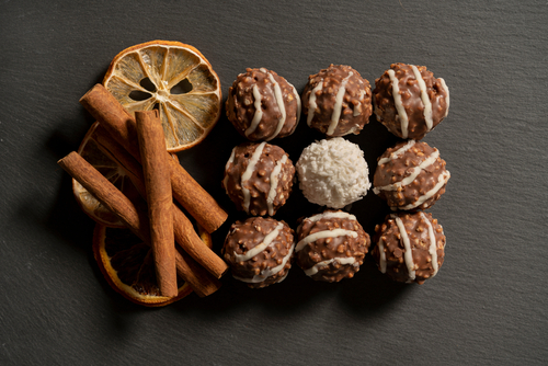 Chocolate,Balls,With,Nuts,And,Cinnamon,On,Gray,Background.