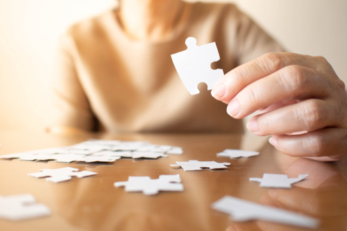 Elderly,Female,Hands,Trying,To,Connect,Pieces,Of,White,Jigsaw