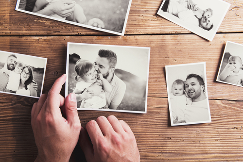 Black,And,White,Family,Photos,Laid,On,Wooden,Floor,Background.